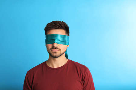128859805 young man with blindfold on blue background space for