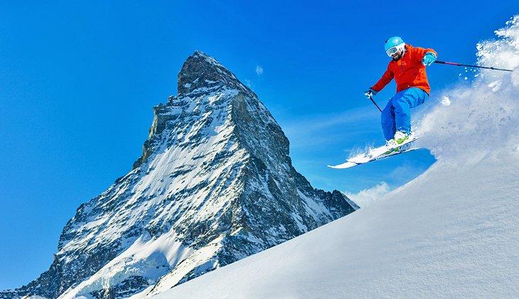 A skier in fresh powder next to the Matterhorn