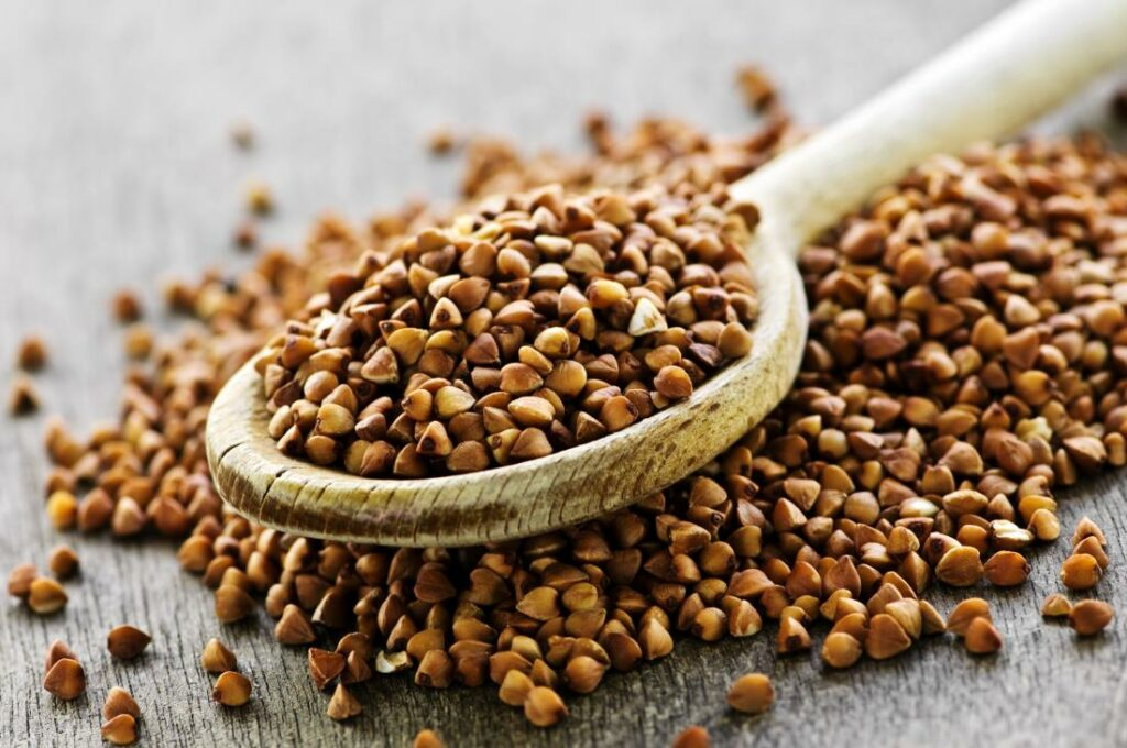dried buckwheat grains on a wooden spoon