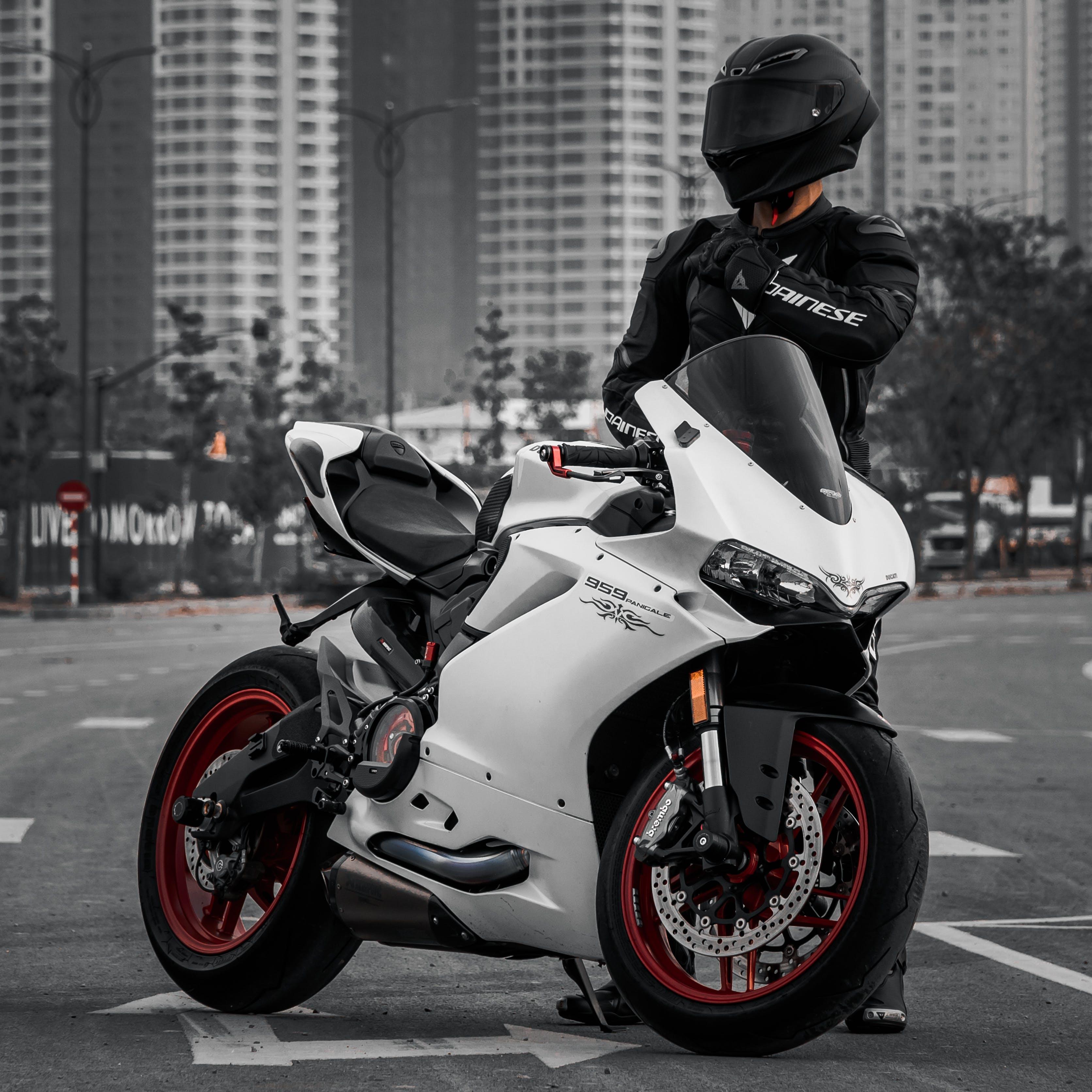 Man in Black Jacket Riding White Sports Bike